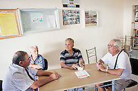 SCIACCA, ITALY - 31 JULY 2012: Elderly men play cards in an unauthorized bowls club in the basement of the unfinished sports club pool in Sciacca, Italy, on July 31, 2012. Series of photographs of unfinished developments in southern Italy.<br /> <br /> CREDIT: Gianni Cipriano for The Wall Street Journal