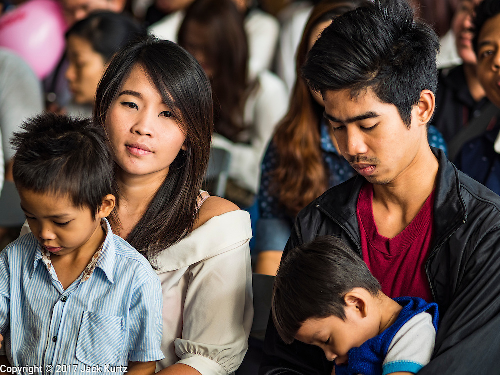 """14 FEBRUARY 2017 - BANGKOK, THAILAND:  A couple, with their children, waits to get married in the Bang Rak district in Bangkok. Bang Rak is a popular neighborhood for weddings in Bangkok because it translates as """"Village of Love."""" (Bang translates as village, Rak translates as love.) Hundreds of couples get married in the district on Valentine's Day, which, despite its Catholic origins, is widely celebrated in Thailand.     PHOTO BY JACK KURTZ"""