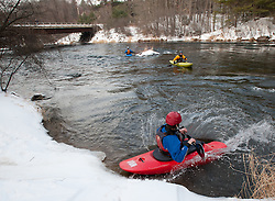 "A kayaker slides into the Winnipesaukee River in Northfield in the ""put in"" area of the 30th annual New Year's Day kayak run on Saturday, January 1, 2011.  (Alan MacRae/for the Monitor)"
