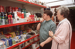 Mother and adult son with Downs Syndrome shopping in supermarket,