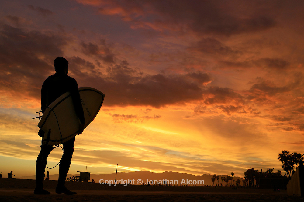 A surfer walks on the bike path during a vivid summer sunset