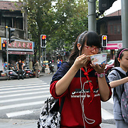 Shanghai, China: Young women eat on the go in Shanghai, one of the most densely populated cities in China with over 24 million residents. .Jose More Photography