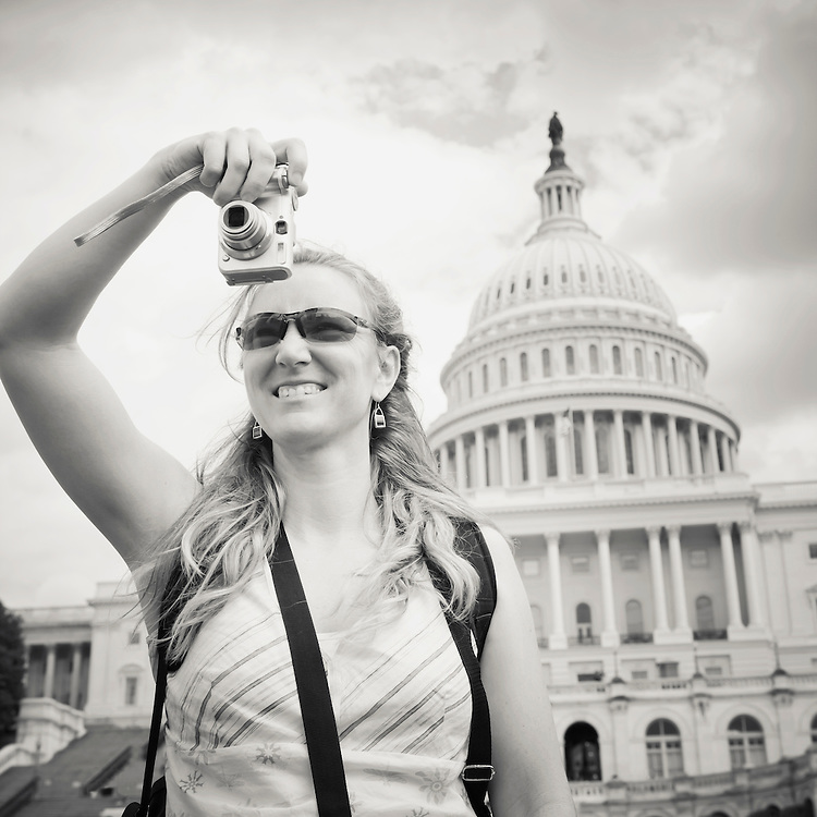 Woman taking a digital picture in front of the US Capitol building, Washington DC, USA.