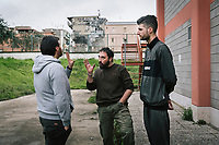 """NAPLES, ITALY - 16 MARCH 2018: (R-L) Vice-President of """"Il Tappeto di Iqbal"""" Marco Riccio (25) and Founder and President Giovanni Savino (38) listen to the Save The Children project coordinator Luigi Malcangi at """"Il Tappeto di Iqbal"""" (Iqbal's carpet), a non-profit cooperative in Barra, the estern district of Naples, Italy, on March 16th 2018.<br /> <br /> Il Tappeto di Iqbal (Iqbal's Carpet) is a non-profit cooperative founded in 2015 and Save The Children partner since 2015 that operates in the Naple's eastern neighborhood of Barra children in the arts of circus, theater and parkour. It was named after Iqbal Masih, a Pakistani boy who escaped from life as a child slave and became an activist against bonded labor in the 1990s.<br /> Barra, which is home to some 45,000 people, has the highest rate of school dropouts in the Italian region of Campania. Once a thriving industrial community, many of the factories were destroyed in a 1980 earthquake and never rebuilt. The resulting de-industrialization turned Barra into a poor, decaying neighborhood. There are no cinemas, theaters, parks or public spaces in Barra.<br /> The vast majority of children from poor families are faced with the choice of working in the black economy or joining the ranks of the organised crime.<br /> Recently, Save the Children Italy opened a number of educational and social spaces in Barra. The centers, known as Punti Luce, or points of light, aim to help local kids stay out of the ranks of the organised crime and have also become hubs for Iqbal's Carpet to work."""