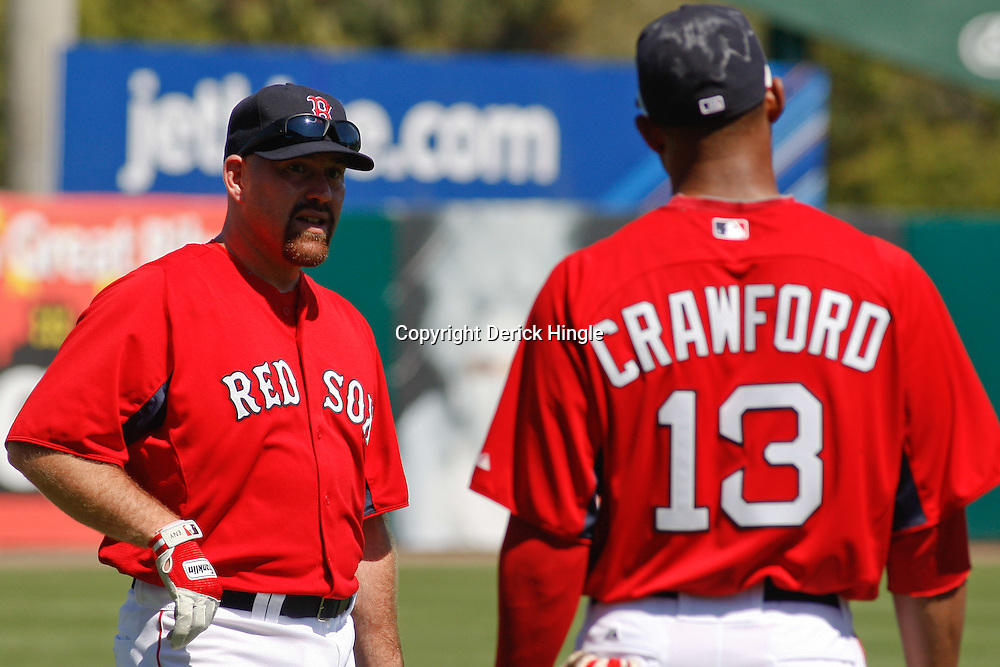 March 7, 2011; Fort Myers, FL, USA; Boston Red Sox third baseman Kevin Youkilis (20) and left fielder Carl Crawford (13) during a spring training exhibition game against the Baltimore Orioles at City of Palms Park.   Mandatory Credit: Derick E. Hingle