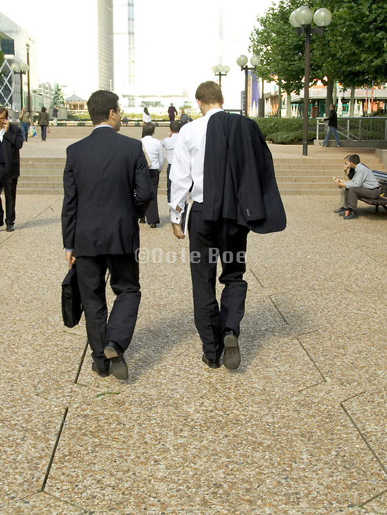 two young businessmen strolling and discussing
