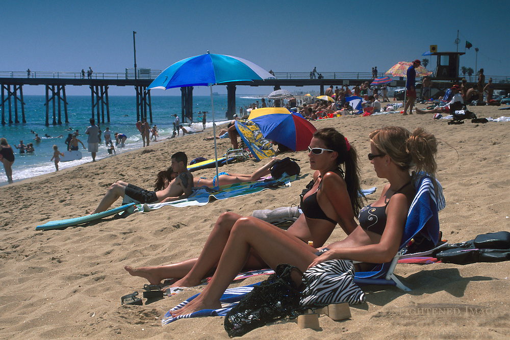Young women in sunbathing on crowded sand beach at Balboa Pier, Newport Beach, Orange County, California