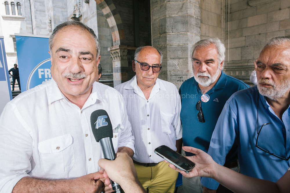 COMO, ITALY - 21 JUNE 2017:  Mario Landriscina (left), the leading candidate for Mayor of Como who wants to close the migrants reception center, answers questions at a journalist at the end of his rally in Como, Italy, on June 21st 2017.<br /> <br /> Residents of Como are worried that funds redirected to migrants deprived the town&rsquo;s handicapped of services and complained that any protest prompted accusations of racism.<br /> <br /> Throughout Italy, run-off mayoral elections on Sunday will be considered bellwethers for upcoming national elections and immigration has again emerged as a burning issue.<br /> <br /> Italy has registered more than 70,000 migrants this year, 27 percent more than it did by this time in 2016, when a record 181,000 migrants arrived. Waves of migrants continue to make the perilous, and often fatal, crossing to southern Italy from Africa, South Asia and the Middle East, seeing Italy as the gateway to Europe.<br /> <br /> While migrants spoke of their appreciation of Italy&rsquo;s humanitarian efforts to save them from the Mediterranean Sea, they also expressed exhaustion with the country&rsquo;s intricate web of permits and papers and European rules that required them to stay in the country that first documented them.