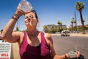 "20 JUNE 2012, PHOENIX, AZ:   A homeless woman provides water over her head in Phoenix, AZ, Wednesday. June 20 is the first day of summer in the northern hemisphere. The high temperature in Phoenix Wednesday soared to over 110 (F), well above the normal of 105. The hot weather is especially stressful on the homeless, who don't have the opportunity to get into air conditioning or access to cold water. ""I Will Listen,"" an outreach organization that assists the homeless and community of street people in Phoenix, AZ, provides free food and cold drinks to the homeless in central Phoenix. They ran out of drinks and food in about one hour during Wednesday's outreach.      PHOTO BY JACK KURTZ"