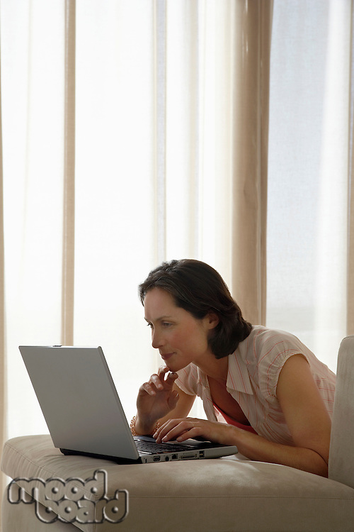 Woman using laptop leaning on sofa cushion