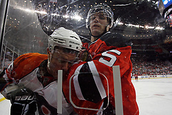 Oct 3, 2009; Newark, NJ, USA; New Jersey Devils defenseman Colin White (5) hits Philadelphia Flyers center Darroll Powe (36) during the third period at the Prudential Center. The Flyers defeated the Devils 5-2.
