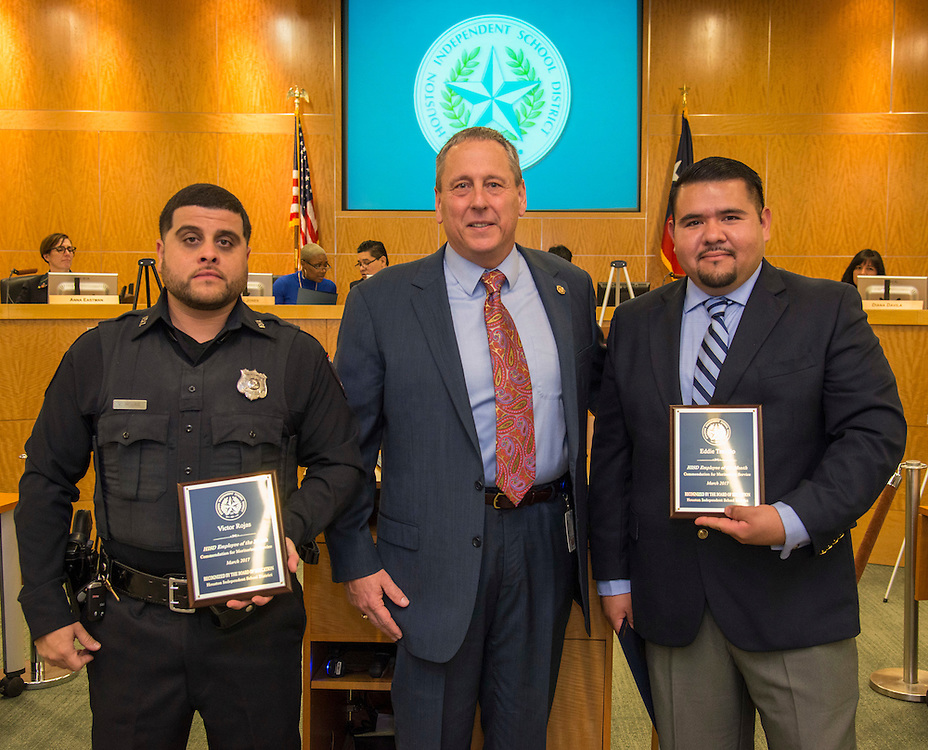 Chief Robert Mock, center, recognizes Officers Victor Rojas, left, and Eddie Treviño, right, as Employees of the Month during a meeting of the Houston ISD Board of Trustees, February 9, 2017.