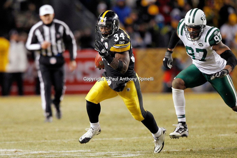Pittsburgh Steelers running back Rashard Mendenhall (34) runs the ball for a 35 yard gain in the second quarter while New York Jets linebacker Calvin Pace (97) chases him during the NFL 2011 AFC Championship playoff football game against the New York Jets on Sunday, January 23, 2011 in Pittsburgh, Pennsylvania. The Steelers won the game 24-19. (©Paul Anthony Spinelli)