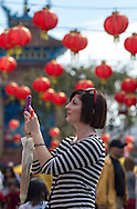 "A tourist takes pictures before  the 114th annual Chinese New Year ""Golden Dragon Parade"" in the streets of Chinatown in Los Angeles, Saturday Feburary 16, 2013. (Photo by Ringo Chiu/PHOTOFORMULA.com)."