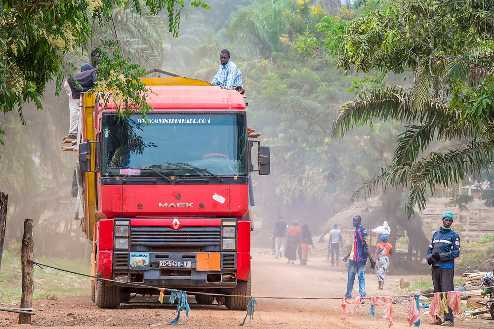 Workers tirelessly load up freight truck with lumber along dirt road, Republic of Guinea