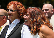 "Tonia Hughes, right, smiles as she lays her chin on the shoulder of her wife, Lisa McGuire, left, as guitarist Reed Waddle, not pictured, sings ""Time After Time"" during the 101 Gay Weddings event put on by Chef Art Smith at the Intercontinental Hotel in Buckhead on Sunday, June 28. (David Welker)"