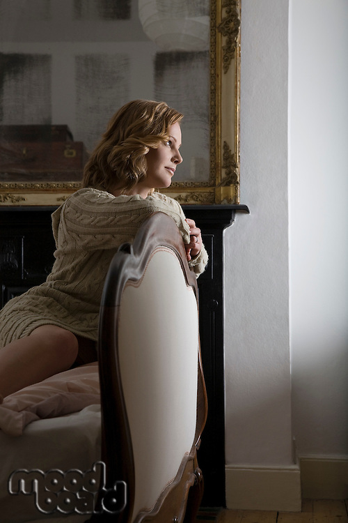 Mid adult woman leaning on chair
