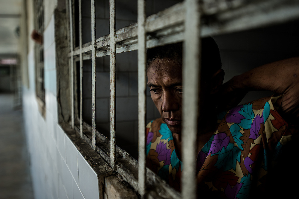 BARQUISIMETO, VENEZUELA - AUGUST 24, 2016: Margarita Silva, a paranoid schizophrenic, looks out of the window of her solitary confinement cell, where she was being held because two days earlier she attacked another patient in the middle of the night, and bit off her nose and ate it. The nursing staff said she had been without two of the medicines she needs to take to control her disorder when the attack occurred, and that they believe that it is unlikely that she would have acted out if she had been medicated, or if she had been under the regular care of a psychiatrist. The economic crisis that has left Venezuela with little hard currency has also severely affected its public health system, crippling hospitals like El Pampero Psychiatric Hospital by leaving it without the resources it needs to take care of patients living there, the majority of whom have been abandoned by their families and rely completely on the state to meet their basic needs. The hospital has not employed a psychiatrist for over two years. Drugs used to combat bipolar disorder, epilepsy, schizoaffective disorder and chronic anxiety are now in short supply, as are numerous sedatives and tranquilizers needed to care for patients. Members of the nursing staff debate daily which patients are the most unstable, to decide which patients will receive pills and which will go without. When a patient loses control, often the only thing they can do is restrain them, or lock them in an isolation cell to prevent them from hurting themselves, other patients and members of the staff.  PHOTO: Meridith Kohut