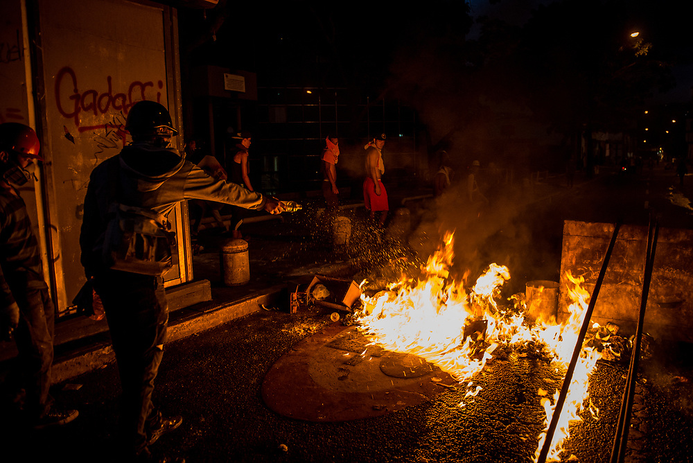 CARACAS, VENEZUELA - MAY 8, 2017:  Anti-government protesters man a road block between clashes with security forces at night.  The streets of Caracas and other cities across Venezuela have been filled with tens of thousands of demonstrators for nearly 100 days of massive protests, held sincde April 1st. Protesters are enraged at the government for becoming an increasingly repressive, authoritarian regime that has delayed elections, used armed government loyalist to threaten dissidents, called for the Constitution to be re-written to favor them, jailed and tortured protesters and members of the political opposition, and whose corruption and failed economic policy has caused the current economic crisis that has led to widespread food and medicine shortages across the country.  Independent local media report nearly 100 people have been killed during protests and protest-related riots and looting.  The government currently only officially reports 75 deaths.  Over 2,000 people have been injured, and over 3,000 protesters have been detained by authorities.  PHOTO: Meridith Kohut