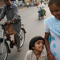 "Vasanti with her youngest daughter Vrinda after collecting her from school in Sangli. ..Like many of the women who work for and with UNDP partners the Save Foundation, Vasanti Shinde only found out that she was HIV positive after her husband became seriously ill with an AIDS-related illness five years ago. Vasanti's husband subsequently died. Vasanti now lives with her two younger daughters Shrudha, age 10, and Vrinda, 8, in the one-room home of her brother in Sangli city. Vasanti's elder daughter, eleven year old Shubhada is being brought up by her paternal grandmother and sees her mother during holidays. Vasanti knows that Shubhada is HIV negative and Shruda is positive but anxiety over the result means that she refuses to have Vrinda tested for HIV. For a monthly income of Rs.3500, Vasanti works as a field officer and counselor for the Save Foundation. She works in the positive-people's pharmacy for no pay. Her work with the Save Foundation entitles her access to a credit union which provides low interest loans covering medical expenses. Though first-line drugs and homeopathic medicine keep Vasanti healthy, she is prone to infection and recently suffered a bout of influenza. Vasanti is completely open about her HIV status and most of her neighbours know that she is HIV positive. Vasanti says that ""I used to feel like I was going to die. Now, because of the Save Foundation, I feel like I'm going to live."" ..Photo: Tom Pietrasik.Sangli, Maharashtra. India.August 27th 2008."