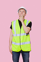 Thoughtful young construction worker looking away over pink background
