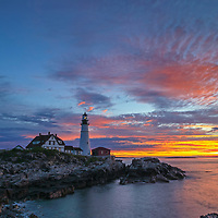 Maine, worth a visit, worth a lifetime featuring the Portland Head Light at Fort Williams Park. This classic New England lighthouse is located on Cape Elizabeth in Maine. It towers high over the swirling Atlantic Ocean and seacoast, marking the entrance to Casco Bay and Portland. Upon arrival, the gates to the park were already open leaving me enough time to scout for an appropriate composition that allows to incorporate the anticipated magical morning show in the sky and some of the dramatic seascape of coastal Maine.<br />