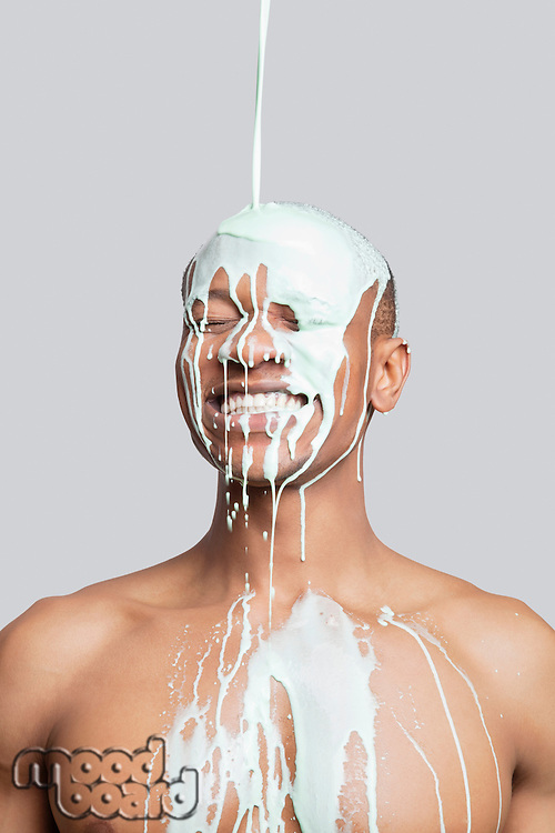 Paint falling on happy shirtless young man's head against gray background
