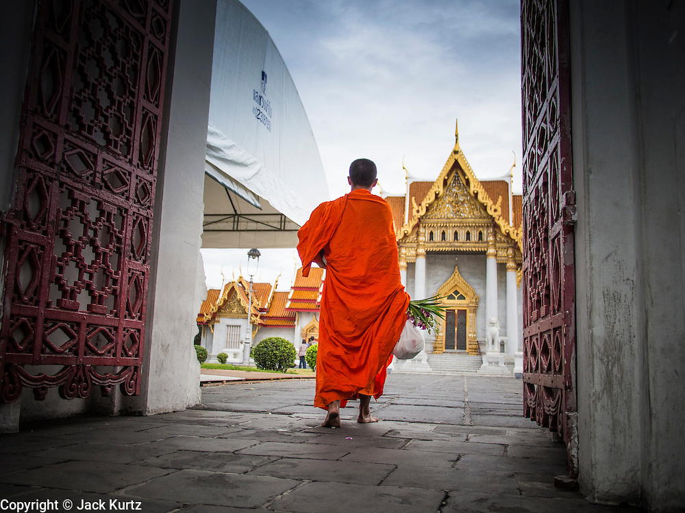 """21 JULY 2013 - BANGKOK, THAILAND:   A Buddhist monk walks into Wat Benchamabophit on the first day of Vassa, the three-month annual retreat observed by Theravada monks and nuns. On the first day of Vassa (or Buddhist Lent) many Buddhists visit their temples to """"make merit."""" During Vassa, monks and nuns remain inside monasteries and temple grounds, devoting their time to intensive meditation and study. Laypeople support the monastic sangha by bringing food, candles and other offerings to temples. Laypeople also often observe Vassa by giving up something, such as smoking or eating meat. For this reason, westerners sometimes call Vassa the """"Buddhist Lent.""""      PHOTO BY JACK KURTZ"""