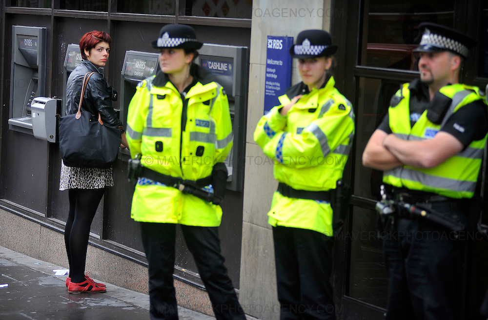EDINBURGH, UK - 23rd August 2010:  Climate change protesters have begun a day of mass action, targeting, the Royal Bank of Scotland across the city of Edinburgh.  Hundreds of protestors have set up camp next to the banks headquarters at Gogarburn on the outskirts of the city to protest about the banks role in financing oil industry developments. Pictured police protect the entrance of the North Bridge branch while activists protest outside. (Photograph: Callum Bennetts/MAVERICK)