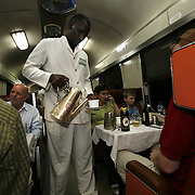 "A waiter serves coffee in the dining car of the Nairobi-Mombasa train. The approximately 300 mile journey took 16 hours this trip. Also known as the ""Lunatic Express"", It was the railway line that built Kenya, linking the port town of Mombasa.through the capital, Nairobi, to the shores of Lake Victoria and on to the.Ugandan capital, Kampala. It cost $5m (in 1894 money) and countless workers died during its construction. There were derailments, collisions, tribal raids and attacks by lions. Yet despite becoming one of Kenya's national treasures and a vital economic artery for east Africa, the railway now lies in a state of disrepair. A South African consortium has taken it over and plans to invest millions, returning it to its former glory. But there has been a row over the railway's financing which may yet derail the .project. .."