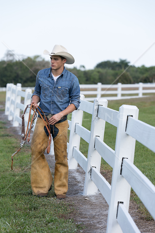 cowboy with bridle reins walking on a ranch