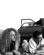 Woman and man lying on a blanket on the grass, beside car, 2000's,