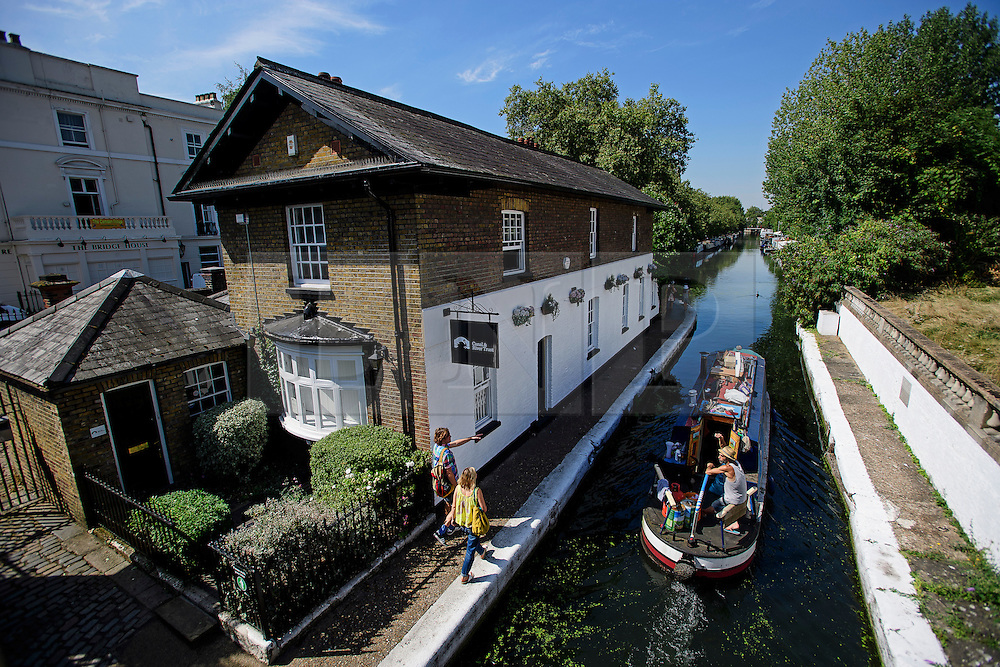 © Licensed to London News Pictures. 24/08/2016. London, UK. A canal boat makes its way along the Grand Union Canal in Little Venice, West London as warm weather across the UK continues.. Photo credit: Ben Cawthra/LNP