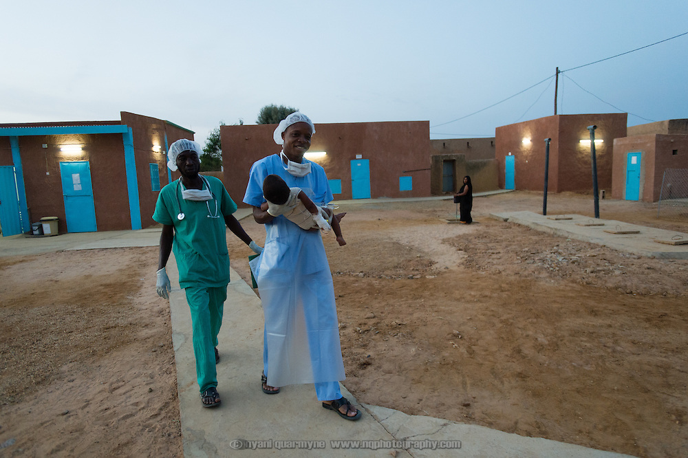 Theatre Nurse, Jean Soro (right), and anesthisiologist, Moussa Kondo Kalla, taking Ahamad Ibrahim (19 months) to an observation ward after the treatment of his burns at the recently completed MSF surgical unit in Bassikounou, Mauritania on 2 March 2013. Now that the surgical unit is operational, surgical emergencies no longer have to be referred to the nearest government hospital, which is six hours away.