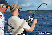 "fishing mate Walter ""Rooster"" Morehead gives advice while angler Jon Givens brings in line while fishing on Reel Addiction, Vava'u, Kingdom of Tonga, South Pacific"