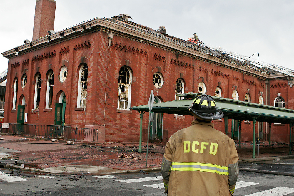 A tired fire fighter contemplates the remnants of the Historic Eastern Market.