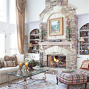 The fieldstone fireplace is the focal point of the living room, and is part of the Colonial Revival style on the houses' exterior.