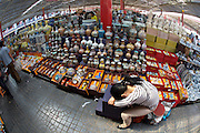 Panjiayuan weekend market. Porcelaine and ceramics seller having a nap.