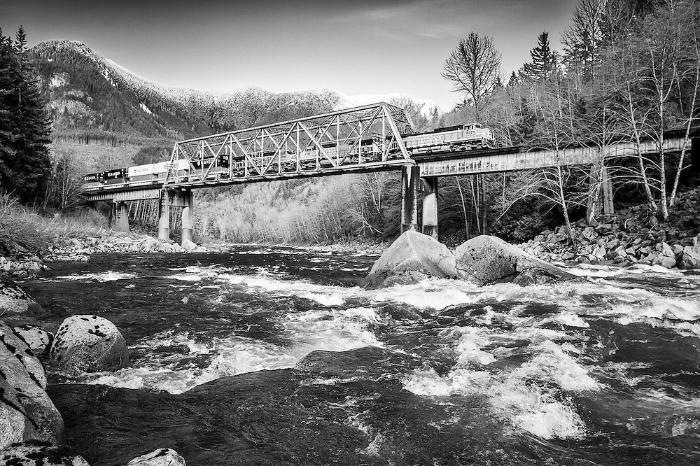 An eastbound intermodel crosses the Skykomish River on its attack of the long grade towards the summit of Steven's Pass. This bridge was originally built in 1892 and was located in the town of Index, 7 miles up stream. In 1962, as part of a Great Northern realignment project between Gold bar and Index, this truss span was moved and reassembled here to allow the line to switch sides of the river.