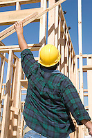 Construction worker holding planks, back view