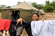 "Khanthong Donsenvong from the Mines Advisory Group female team hangs her clothes to dry.  The women working in Khammuan Province live in tents working in remote locations with no electricity, showers or toilets.  They wash in the river and use the forest as a latrine. They work in 4 week cycles, with 3 weeks straight working and one week off to return home and see family.  The girls joked, ""We are more afraid of the leaches, because they will chase you, but the bombs they don't move.""..Laos was part of a ""Secret War"", waged within its borders primarily by the USA and North Vietnam.  Many left over weapons supplied by China and Russia continue to kill.  However, between 90 and 270 million fist size cluster bombs were dropped on Laos by the USA, with a failure rate up to 30%.  Millions of live cluster bombs still contaminate large areas of Laos causing death and injury.  The US Military dropped approximately 2 million tons of bombs on Laos making it, per capita, the most heavily bombed country in the world. ..The women of Mines Advisory Group (MAG) work everyday under dangerous conditions removing unexploded ordinance (UXO) from fields and villages...***All photographs of MAG's work must include (either on the photo or right next to it) the credit as follows:  Mine clearance by MAG (Reg. charity)***."