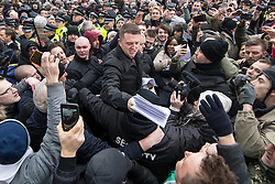 "© Licensed to London News Pictures . 18/03/2018 . London , UK . TOMMY ROBINSON (centre) hands out copies of his speech to the crowd . 1000s including supports of alt-right groups such as Generation Identity and the Football Lads Alliance , at Speakers' Corner in Hyde Park where Tommy Robinson reads a speech by Generation Identity campaigner Martin Sellner . Along with Brittany Pettibone , Sellner was due to deliver the speech last week but the pair were arrested and detained by police when they arrived in the UK , forcing them to cancel an appearance at a UKIP "" Young Independence "" youth event , which in turn was reportedly cancelled amid security concerns . Photo credit: Joel Goodman/LNP"