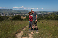 Mike and Diana Ellis hug on a summer day after hiking to a point that looks over Petaluma, California.