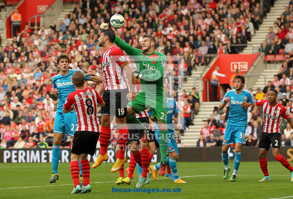 Fraser Forster (centre) of Southampton punches the ball clear during the Barclays Premier League match at the St Mary's Stadium, Southampton<br /> Picture by Tom Smith/Focus Images Ltd 07545141164<br /> 18/10/2014