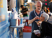 Mitch Moore feeds Sharon Moore a french fry at the Xerox Rochester International Jazz Festival on Sunday, June 22, 2014.