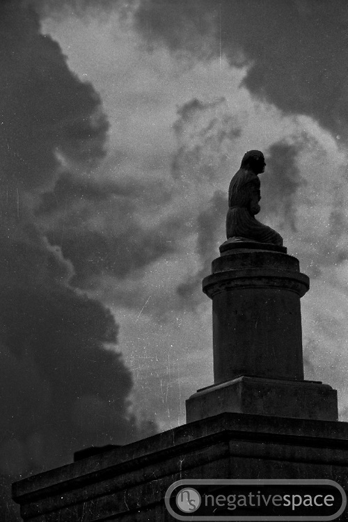 Statue under the oncoming storm, St. Louis Cemetary, New Orleans, Louisiana