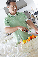 Man chopping peppers in kitchen