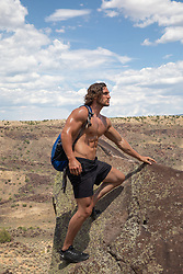 shirtless muscular male hiker on top of a mountain in New Mexico