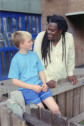 Boy and carer talking outside entrance to block of flats,