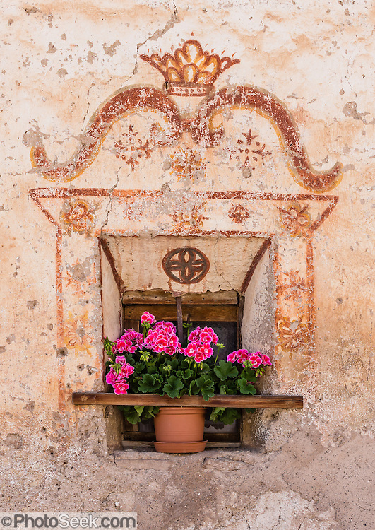 Old window with fresco and flowers, in St. Magdalena (Santa Maddalena) village in the valley and municipality of Funes (Villnöss) in Trentino-Alto Adige/Südtirol (South Tyrol), Italy. Enjoy great hiking here in the vast Nature Park of Parco Naturale Puez-Odle (German: Naturpark Puez-Geisler; Ladin: Parch Natural Pöz-Odles). The Dolomites are part of the Southern Limestone Alps, in Europe. UNESCO honored the Dolomites as a natural World Heritage Site in 2009.